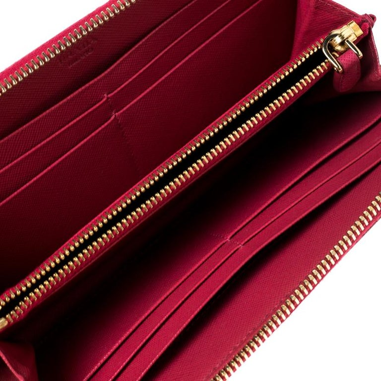 This wallet from Prada is one creation a fashionista like you must own. It has been wonderfully crafted from dark pink Saffiano lux leather. The gold-tone top zipper opens to reveal a leather-fabric lined interior featuring multiple card slots and a