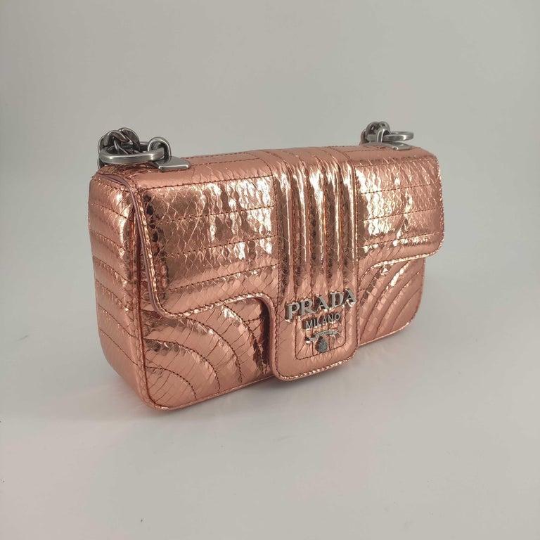 - Designer: PRADA - Model: Diagramme - Condition: Never worn.  - Accessories: Dustbag, Authenticity Card - Measurements: Width: 22cm, Height: 13cm, Depth: 5cm, Strap: 120cm - Exterior Material: Leather - Exterior Color: Pink - Interior Material:
