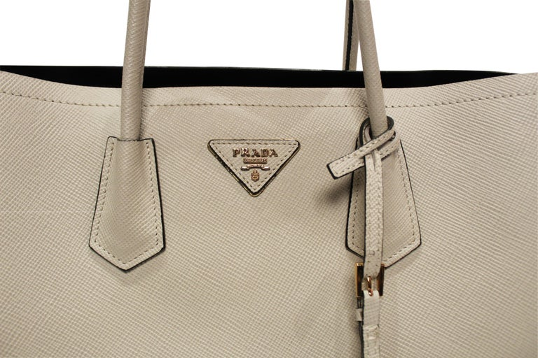 Light Beige Saffiano leather PRADA Double Bag in medium with gold toned hardware. This structured and spacious bag provides dual compartments, divided by interior flap pocket for valuables. This gorgeous bag has a soft nappa leather interior and