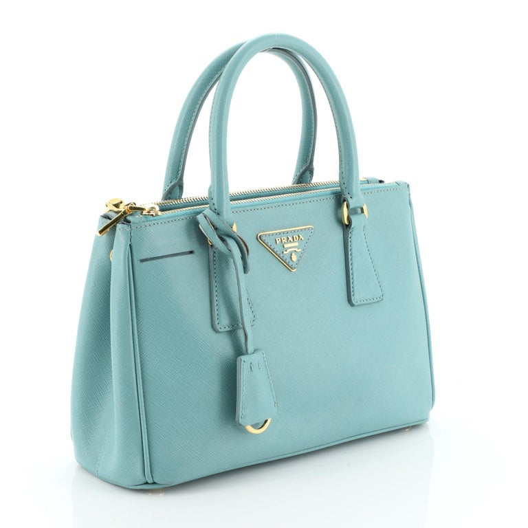 This Prada Double Zip Lux Tote Saffiano Leather Mini, crafted from blue saffiano leather, features dual rolled handles, raised Prada logo plate, and gold-tone hardware. It opens to a blue fabric interior with two zip compartments on both sides and
