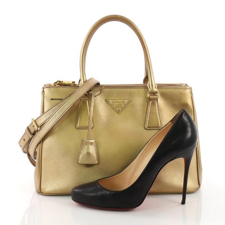 This Prada Double Zip Lux Tote Saffiano Leather Small, crafted from gold saffiano leather, features dual rolled handles, raised Prada logo plate, and gold-tone hardware. It opens to a gold fabric interior with two zip compartments on both sides and