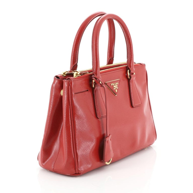 This Prada Double Zip Lux Tote Vernice Saffiano Leather Mini, crafted from red vernice saffiano leather, features dual rolled handles, raised Prada logo plate, and gold-tone hardware. It opens to a red fabric and leather interior with two zip