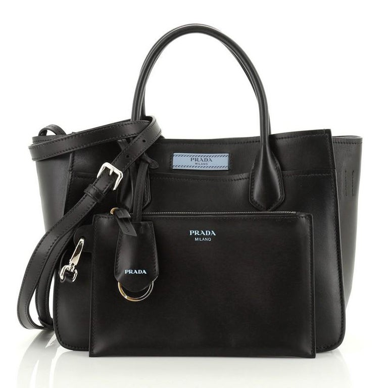 This Prada Dual Shopping Tote Calfskin Medium, crafted from blue calfskin leather, features dual rolled handles, exterior slip compartments and silver-tone hardware. It opens to a blue suede interior.   Estimated Retail Price: $1,950 Condition: Very