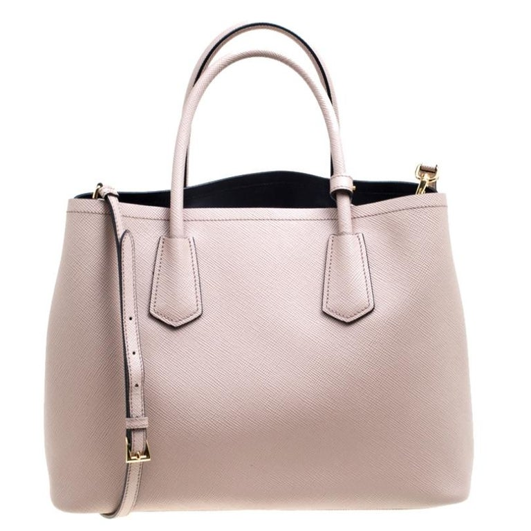 This elegant bag from Prada is reliable and packed with style. Crafted from leather it is perfect for daily use. The bag features double handles, a leather tag, and a removable shoulder strap. The leather lined interior is spacious enough to fit