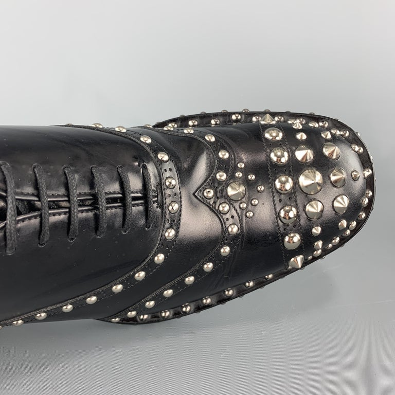 Iconic PRADA Fall / Winter 2009 Collection dress shoes come in polished black leather with a wingtip and silver tone dome and cone spike studs throughout. With box. Made in Italy.  Excellent Pre-Owned Condition. Marked: UK 7.5  Outsole: 12 x 4.5 in.