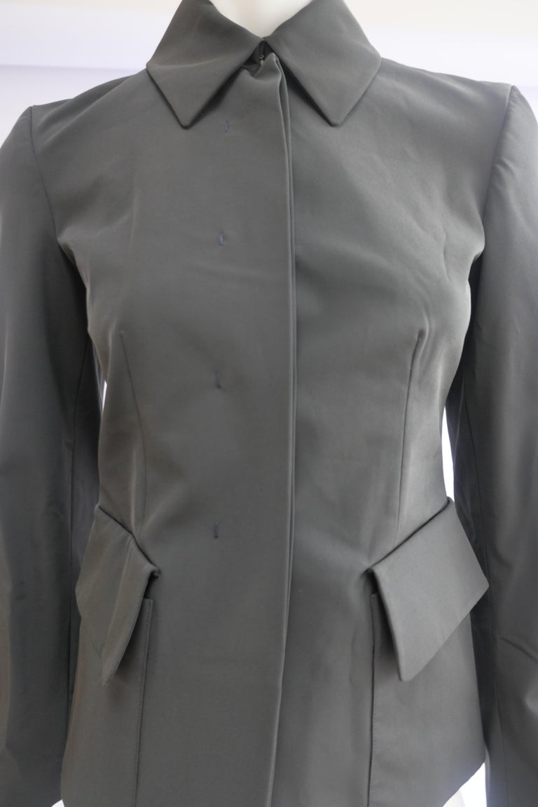 Prada Fitted Jacket 38 Dark Grey  This piece is a fitted Prada jacket with concealed buttons. The design is modern and minimal in the classic Prada design style.  Size:38 Shoulder width: 38 cm  Width: 40 cm  Sleeve length: 60 cm  Length: 56