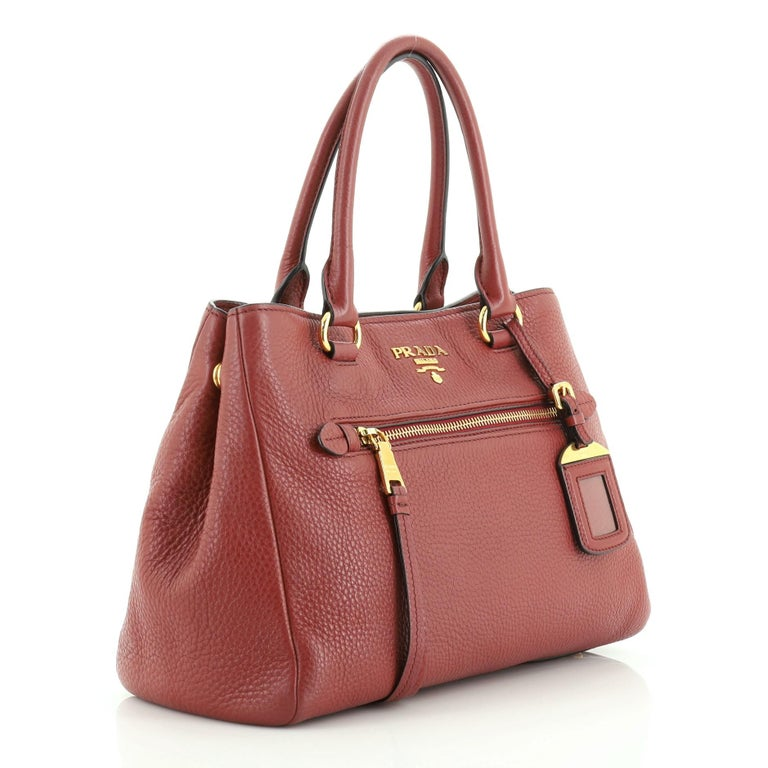 This Prada Front Pocket Convertible Tote Vitello Daino Medium, crafted from red vitello daino leather, features dual rolled leather handles, exterior zip pocket, and gold-tone hardware. Its snap button closure opens to a red fabric interior with