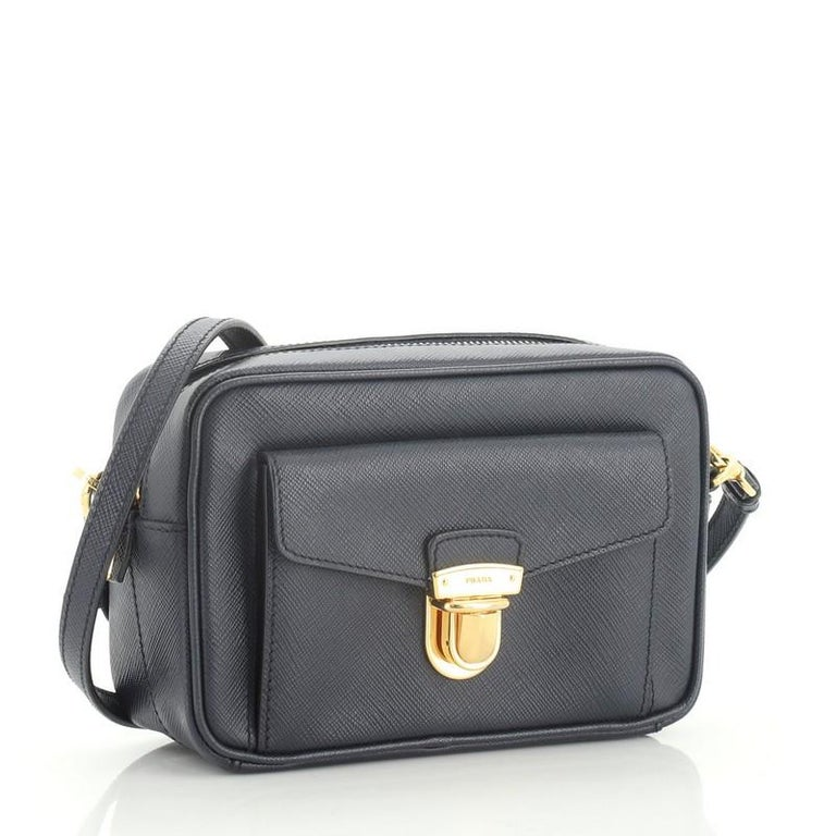 This Prada Front Pocket Zip Crossbody Bag Saffiano Leather Mini, crafted in blue saffiano leather, features an adjustable leather strap, exterior front pocket and gold-tone hardware. Its zip closure opens to a black fabric interior with zip and slip