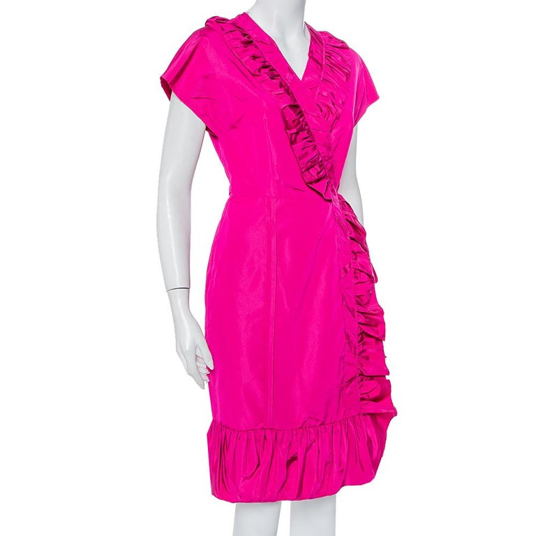Playful and perfect for donning an effortless outfit that still makes a statement, this Prada dress is a beauty. Crafted from a silk blend, this fuchsia pink dress has a wrap silhouette. It comes with short sleeves, ruffle detailing and comfortable