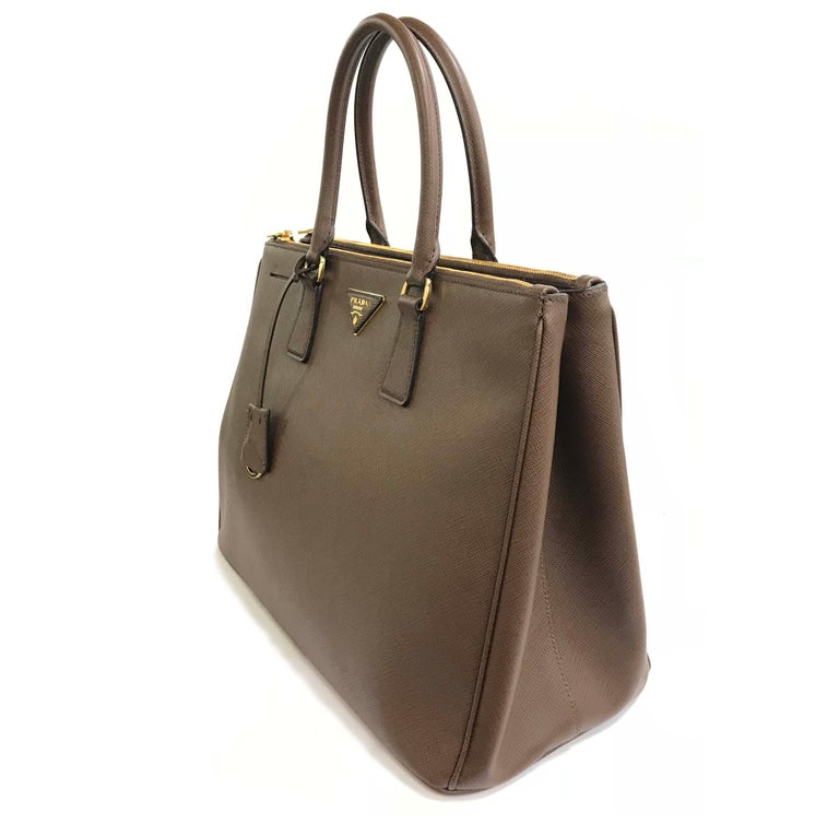33160c537a6c Prada saffiano leather tote bag with golden hardware. Two rolled tote  handles, 5.5