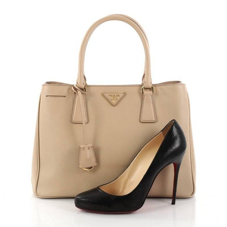 This authentic Prada Gardener's Tote Saffiano Leather Medium is elegant in its simplicity and structure. Crafted from beige saffiano leather, this tote features dual-rolled leather handles, raised Prada logo, protective base studs, and gold-tone