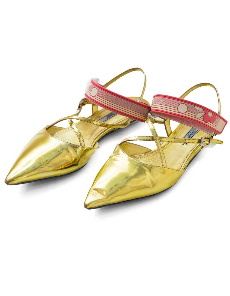 Prada Gold Glazed Leather Flats Sz 38.5  Features pink strap across vamp  Made In: Italy Color: Gold, pink Materials: Glazed leather Closure/Opening: Velcro strap across vamp Sole Stamp: Prada 38.5 Made in Italy Overall Condition: Very good