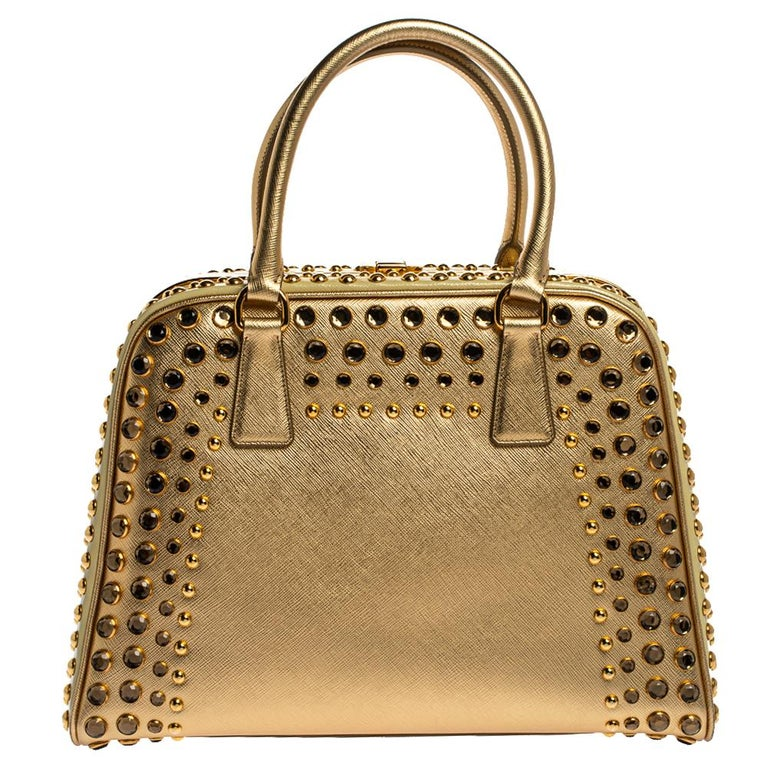 High in appeal and style, this satchel is a Prada creation. It has been crafted from Saffiano lux leather and shaped to exude class and luxury. The bag is adorned with gold-tone studs and comes with two handles and a spacious leather interior for