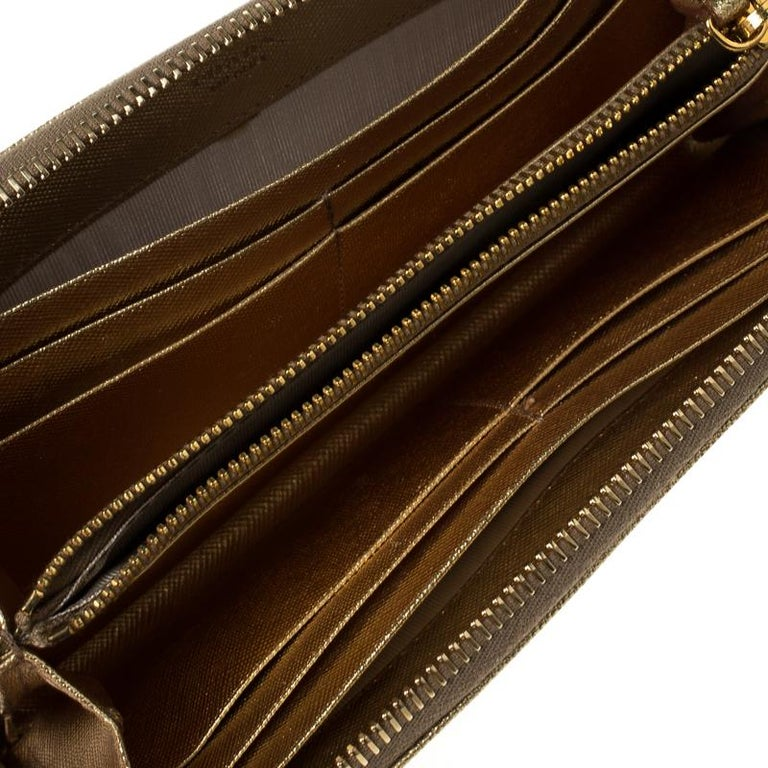 This wallet from Prada is one creation a fashionista like you must own. It has been wonderfully crafted from gold Saffiano metal leather. The gold-tone top zipper opens to reveal a leather-lined interior featuring multiple card slots and a zipped