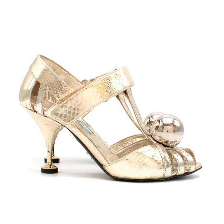Prada Gold Snake Kitten Heels  - Patient Gold snake print leather - T-Strap with velcro closure - Open toe with multiple straps - Large gold ball detail on the toe - Kitten heel with black stopper - Exposed multi-strap detailing  Materials