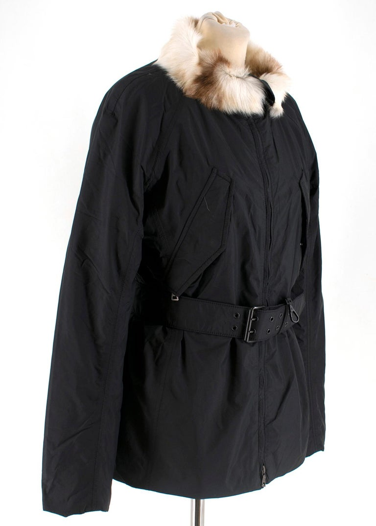 Black warm Prada jacket with a belt to create a flattering silhouette.  A fur collar lining, front zip, inner and outer pockets.   - 100% Nylon - Made in Italy  - Outer shell: 100% Nylon - Padding: 100% Polyester  - Collar lining: 100% Dyed Goat