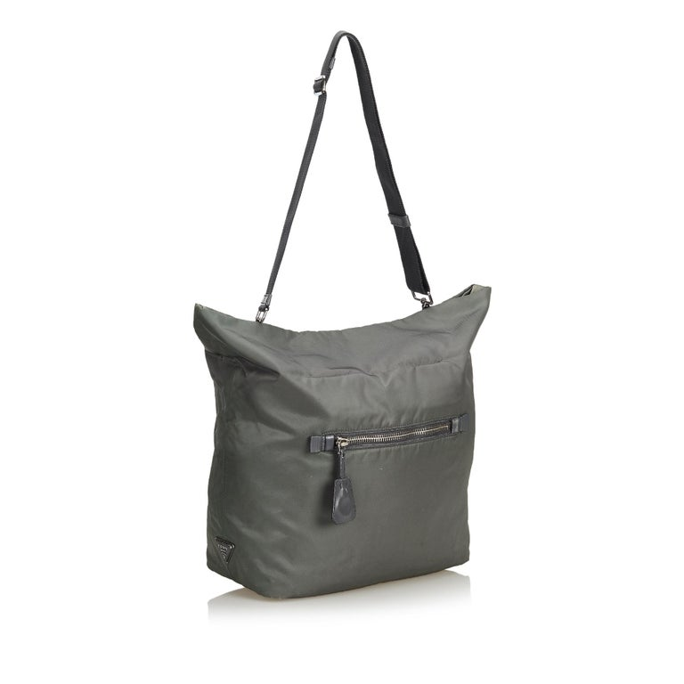 This satchel features a nylon body, rolled leather handles, flat leather strap, open top with magnetic closure, exterior zip pocket and interior zip and slip pockets. It carries as B+ condition rating.  Inclusions:  Dust Bag  Dimensions: Length: