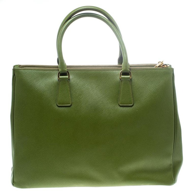 Beautifully crafted from Saffiano Lux leather, this Prada tote is a creation you can't miss. It has a classy green exterior along with two zippers and a spacious nylon interior that will hold your necessities. The bag is held by two handles, and