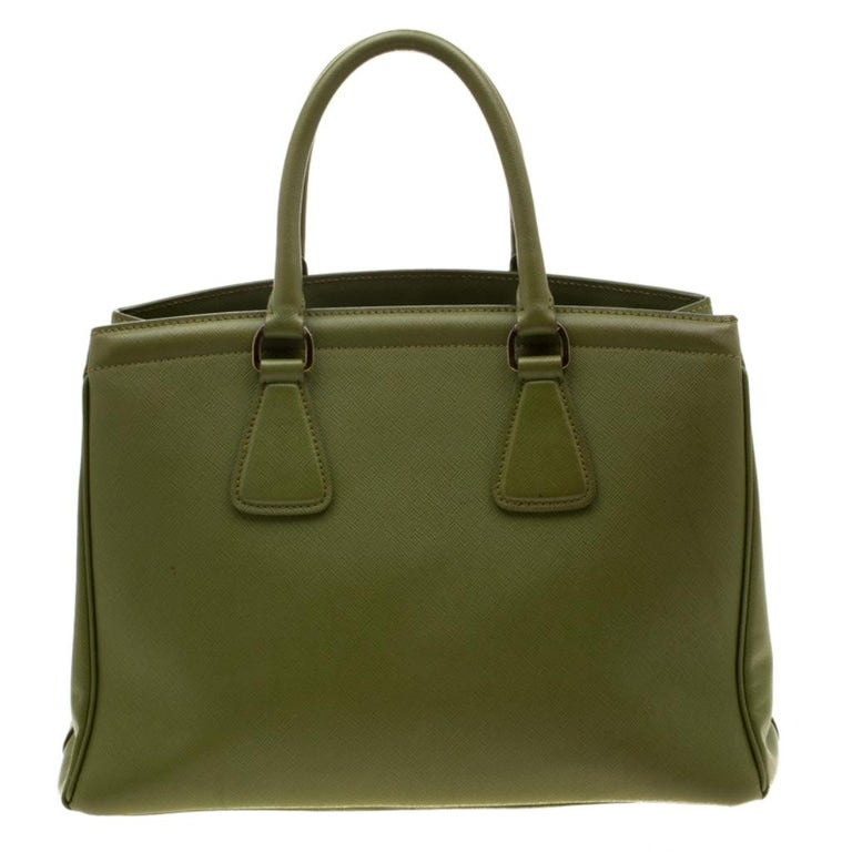 Masterfully created, this Prada tote is a style staple. Designed using Saffiano leather, it exudes style and class in equal measures. This delightful green piece is held by two top handles and equipped with a spacious nylon interior.  Includes: The