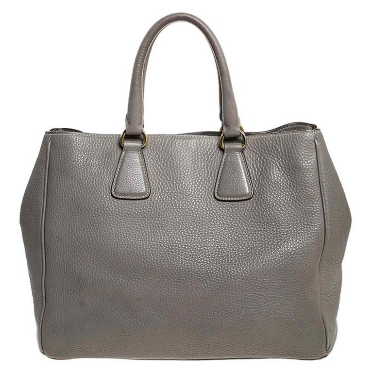 Feel great every time you walk out the door with this well-made leather bag. With the interior lined in nylon, this bag is spacious and stylish. This admirable Prada tote in grey is hed by two handles and finished with the brand name on the