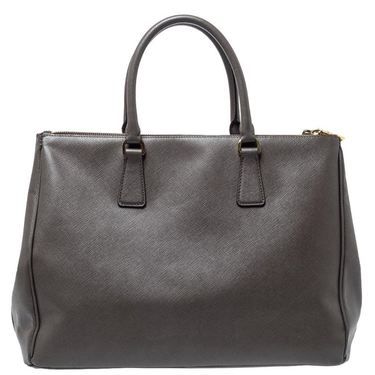 Feminine in shape and grand on design, this Double Zip tote by Prada will be a loved addition to your closet. It has been crafted from Saffiano Lux leather and styled minimally with gold-tone hardware. It comes with two top handles, two zip