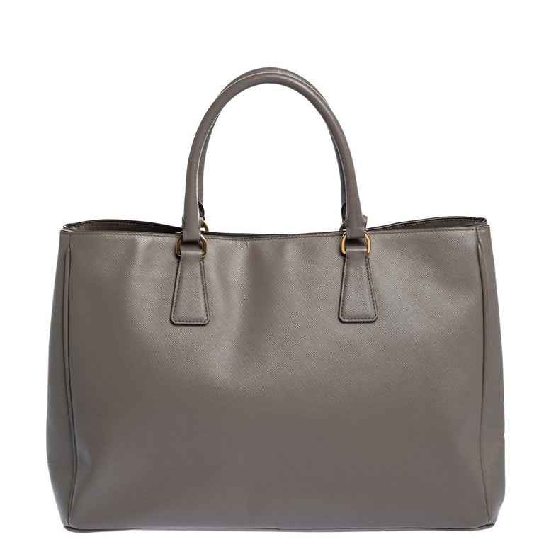 High in appeal and style, this tote is a Prada creation. It has been crafted from Saffiano Lux leather and shaped to exude class and luxury. The grey bag comes with two handles and a spacious nylon interior for your ease. Protective metal feet and
