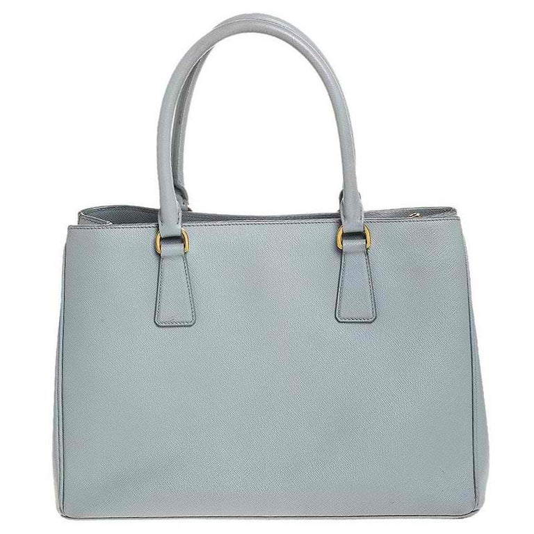 Grand in design, this Galleria tote by Prada will be a loved addition to your closet. It has been crafted from Saffiano Lux leather and styled minimally with gold-tone hardware. It comes with two top handles and a perfectly-sized main compartment.