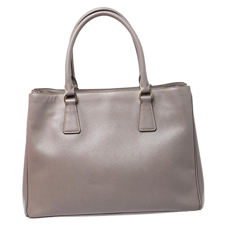 This tote by Prada will be a loved addition to your closet. It has been crafted from Saffiano Lux leather and styled minimally with gold-tone hardware. It comes with two top handles and a nylon interior divided by a zip compartment. The bag is