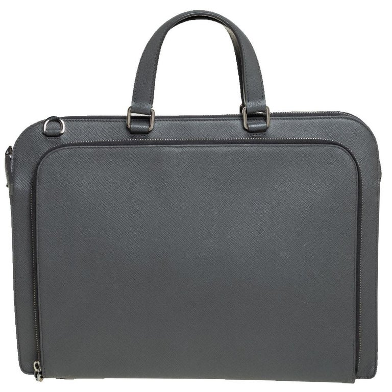 This Prada Travel briefcase brings such a fine shape that you're sure to look fashionable whenever you carry it. The men's briefcase has been crafted from grey Saffiano Lux leather and designed with two handles, zip compartments, and the Prada