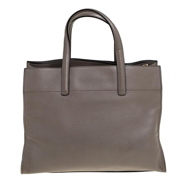 Created from grey Saffiano leather and lined with leather and nylon, this Prada bag is a fine accessory for all your needs. The tote has spacious compartments and two handles for you to parade the beauty. It is stylish, functional and
