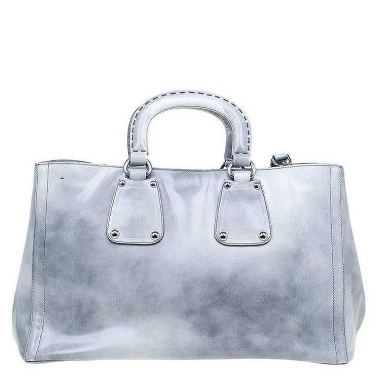 Crafted with glazed calfskin leather, this Prada shopping tote has silver tone details, top handles and an adjustable/removable shoulder strap. It has a spacious interior with a zipped pocket to hold all your essentials. Four protective feet have