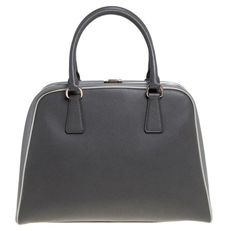 Giving handle bags an elegant update, this Pyramid Frame bag by Prada will be a valuable addition to your closet. It has been crafted from leather and styled with silver-tone hardware. It comes with dual top handles, protective metal feet at the
