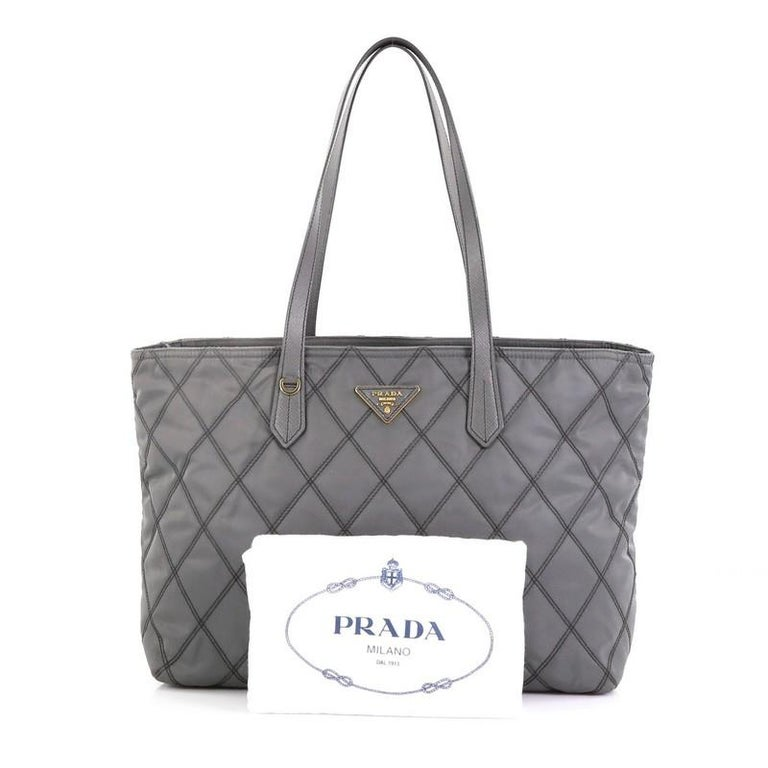 This Prada Impunto Zip Tote Quilted Tessuto Large, crafted in gray tessuto impunto, features dual leather handles, diamond quilted design and gold-tone hardware. Its zip closure opens to a black fabric interior with zip and slip pockets.   Estimated