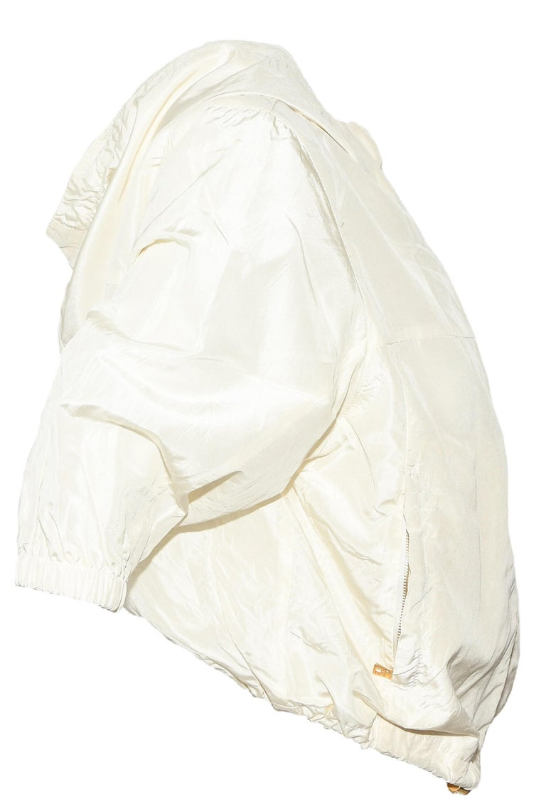 Prada ivory silk blend bomber style jacket contains an attached hoodie and has elastic gather around waistline and around 3/4 length sleeve cuffs.  This cropped jacket has 2 side zippered pockets for essentials and 2 snaps at neck below hoodie