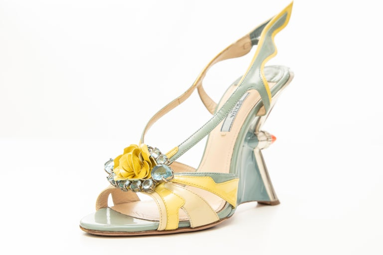 Prada, Spring-Summer 2012 jewel silver-tone taillight wedge sandal with flame accents at sides, floral appliqué at tops featuring crystal embellishments, resin heels with elasticized slingback straps. Includes dust bag.  IT. 40, US. 10  Heels: 5.25