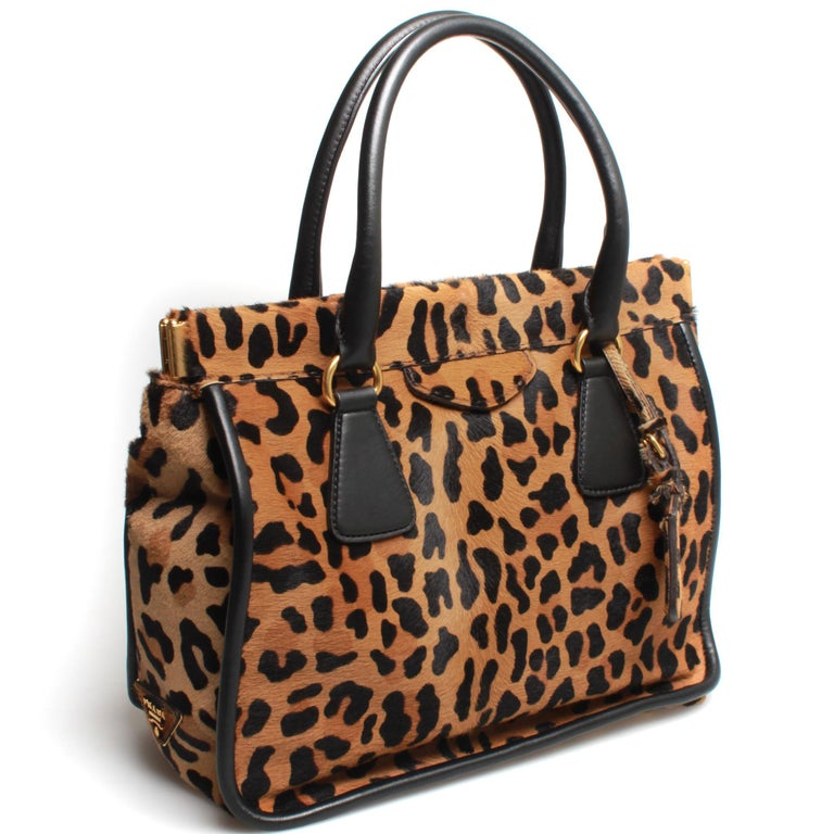 Beautifully structured leopard print PRADA pony hair handbag with gorgeous beige suede interior and dual top handles in black leather.  Comes with original box.  FINAL SALE