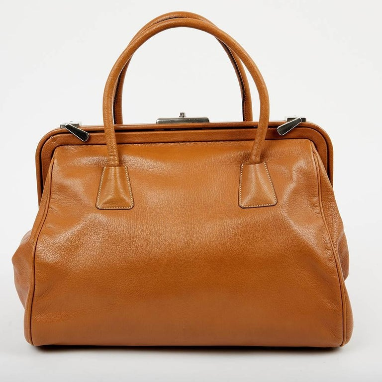 This gorgeous Prada bag is crafted from brown leather and features two rolled top handles. I very good condition with a sign of wear on the right corner (see last picture). It has a doctor's bag shape and silver-tone hardware. The interior is fabric