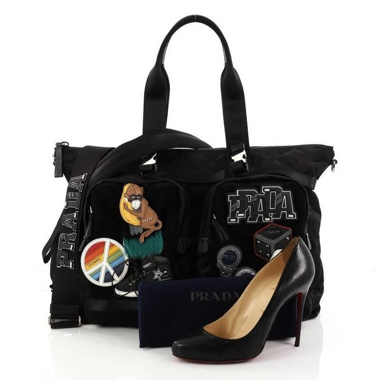 This authentic Prada Limited Edition Patches Tote Quilted Tessuto Large is a one-of-kind collectible bag perfect for Prada lovers. Only produced for Tokyo's Autumn-Winter 2017 Collection presentation, this bag is crafted in black quilted tessuto