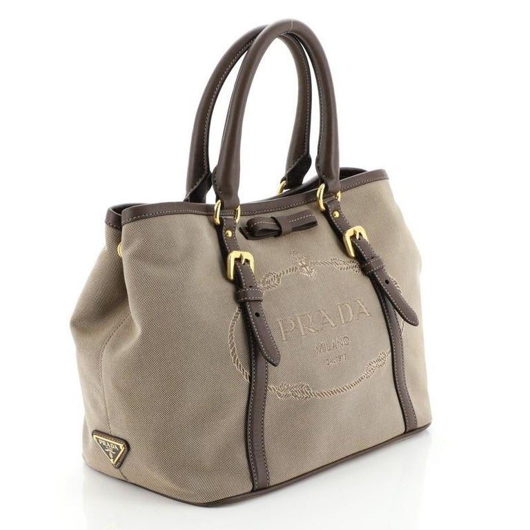 This Prada Logo Convertible Tote Canvas with Leather Medium, crafted in brown canvas, this tote features dual rolled leather handles, embossed Prada logo at the center, and gold-tone hardware. Its magnetic closure opens to a neutral fabric interior