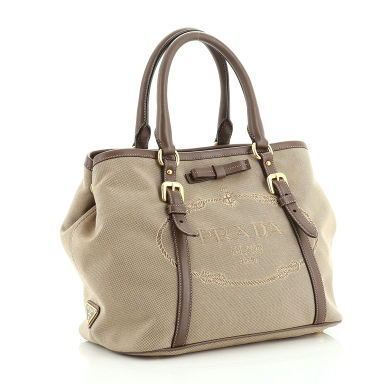 This Prada Logo Convertible Tote Canvas with Leather Medium, crafted from brown leather and canvas, features Prada logo at the front, dual rolled handles and gold tone hardware. It opens to a brown fabric interior with zip pocket.   Estimated Retail
