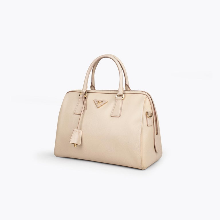 Beige Saffiano leather Prada Lux Zip bag with  - Gold-tone hardware - Dual rolled top handles - Protective feet at base - Logo placard at front - Tonal logo jacquard lining, dual pockets at interior wall; one with zip closure and zip closure at