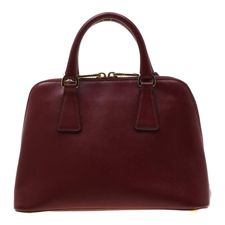 This stunning Promenade tote is high on appeal and style. This classy Prada creation is crafted from saffiano leather and features two rolled handles. The zip closure leads way to nylon interiors with wide space and a center zip pocket. This