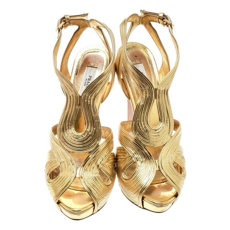 This amazing pair of metallic gold sandals is from Prada. They are crafted from leather and feature cutouts and peep toes. The platform sandals bring ankle straps with buckle fastening and 13 cm heels.  Includes: Extra Beige Tone Top Lifts, Info