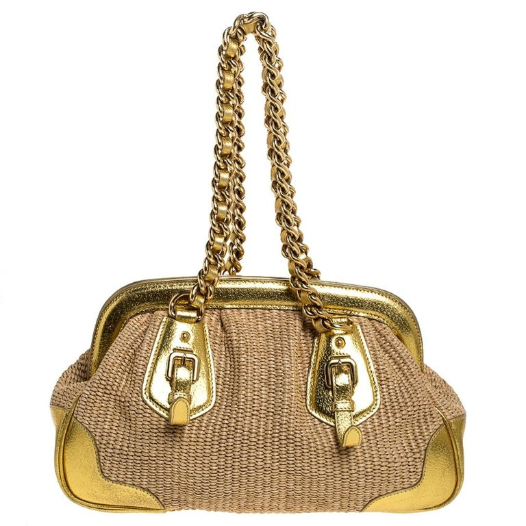This stunning frame bag by Prada is a must-have. It is crafted in Italy and made of quality straw. It comes in a stunning shade of gold and adds a touch of glamour to every outfit. The exterior features leather trims and a brand logo. The bag opens