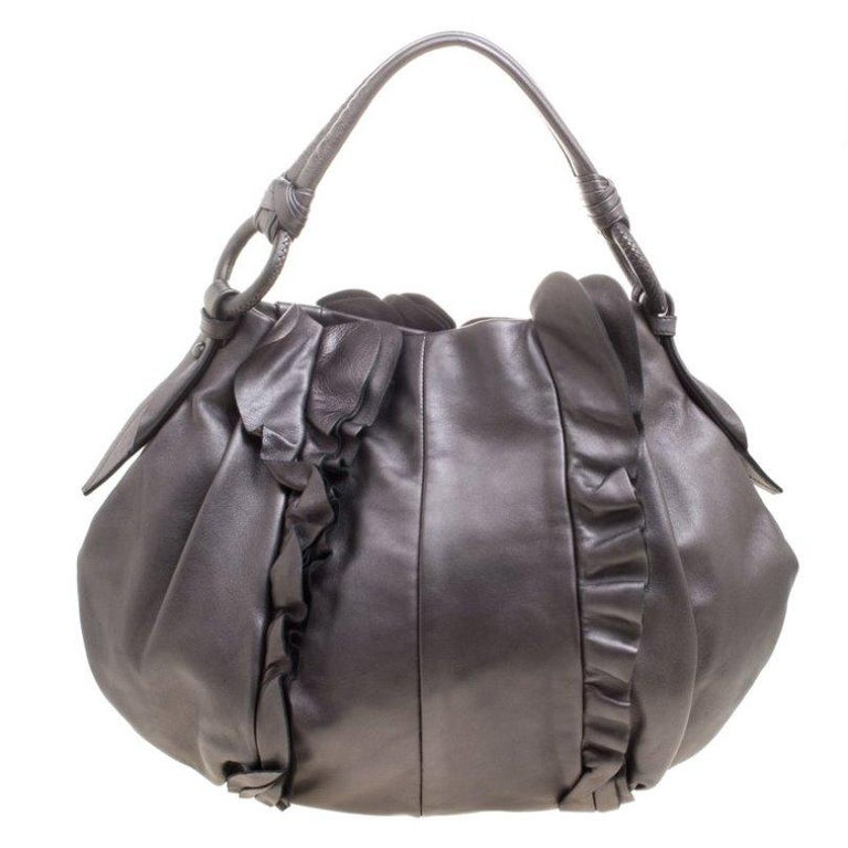 Prada brings to you this hobo that is an absolute delight. Gorgeous in a metallic grey shade, this hobo is crafted from leather and features an artistic ruffle detailing on the front and back. It flaunts a single handle with an attached tag accent