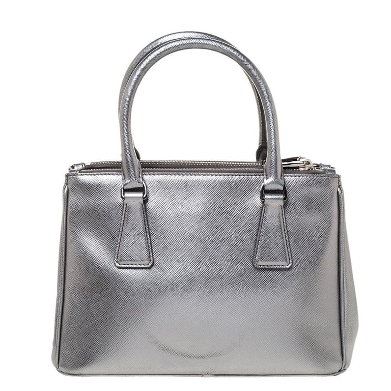 Feminine in shape and grand on design, this Double Zip tote by Prada will be a loved addition to your closet. It has been crafted from metallic silver leather and styled minimally with silver-tone hardware. It comes with two top handles, two zip
