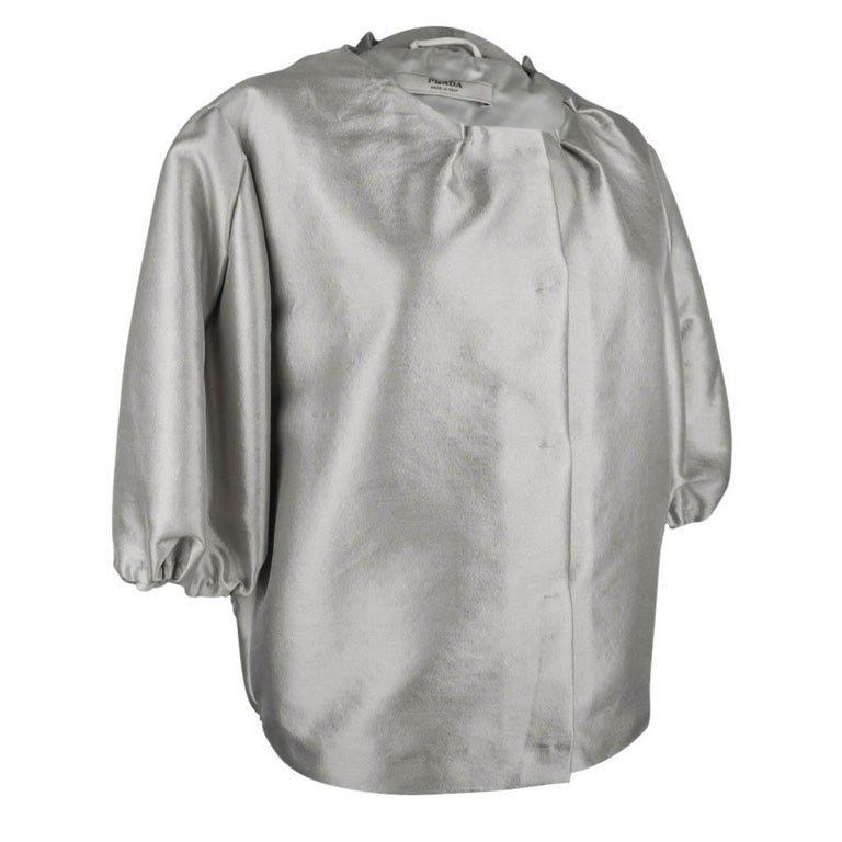 Guaranteed authentic Prada amazing jacket that has real Jackie O - Audrey Hepburn style!   Highly styled silver gray jacket. No collar the neck line is accentuated with small 'catches' with a single stitch. The sleeves end below the elbow in a