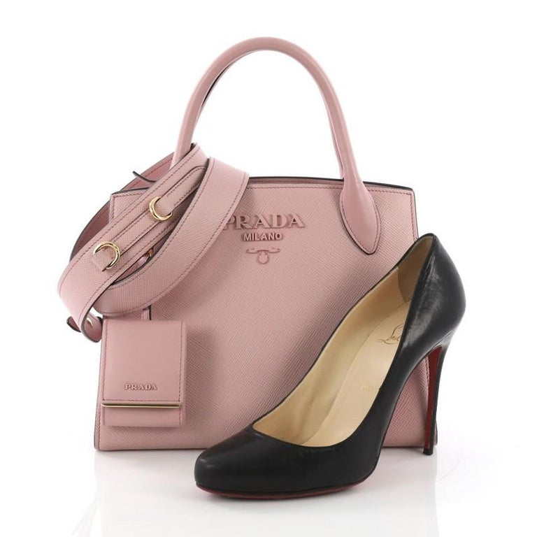 This Prada Monochrome Tote Saffiano Leather with City Calfskin Small, crafted in pink saffiano leather with city calfskin, features dual rolled leather handles, side snap buttons, and gold-tone hardware. It opens to a pink fabric interior with side