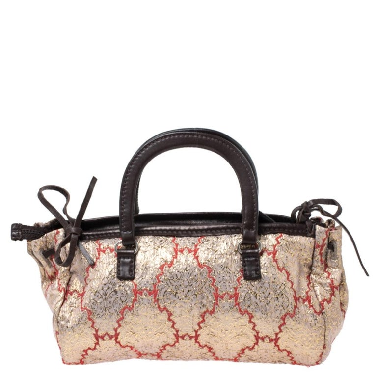 Keep it classy and elegant with this handbag from the house of Prada. Crafted in Italy, it is made of quality brocade fabric and leather. This satchel is classy and exudes sophistication. It is held by dual handles and comes with a top-zip closure