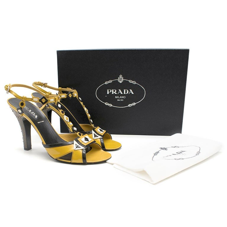 Yellow patent leather heels from Prada with black and white details and a brown, crystal-embellished heel.   - 10 cm Heel - Box and dustbag included  Please note, these items are pre-owned and may show signs of being stored even when unworn and